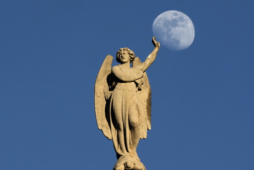 The crescent moon rises behind a statue on the Saint-Germain l'Auxerrois church in central Paris