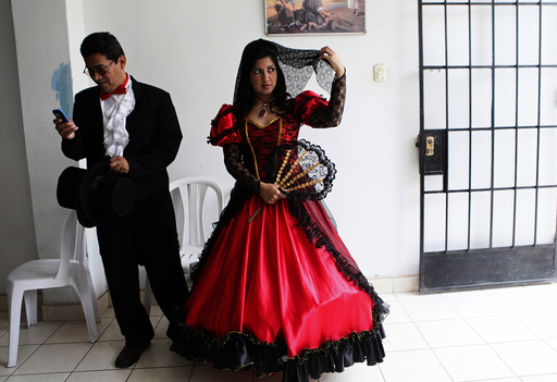 A couple wearing traditional clothes wait for the start of a mass wedding ceremony, in the district of Comas in Lima