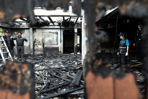 Forensic experts inspect a burnt building at the Pitakkiat Wittaya School in the northern province of Chiang Rai