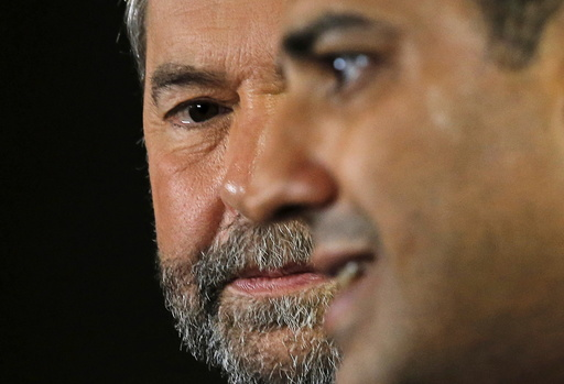 Canada's New Democratic Party leader Thomas Mulcair looks over at freed Al Jazeera journalist Mohamed Fahmy during a news conference in Toronto
