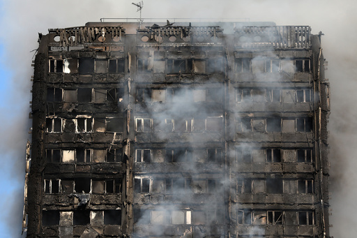 Smoke billows from a tower block severly damaged by a serious fire, in north Kensington, West London