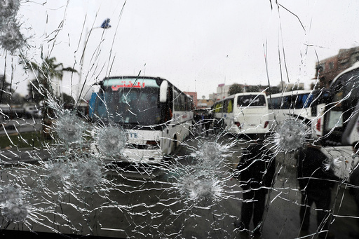 People are seen though a shattered glass window of a bus at the site of an attack by two suicide bombers in Damascus
