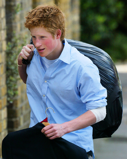 BRITAIN'S PRINCE HARRY CARRIES OUT HIS BELONGINGS AS HE LEAVES ETON COLLEGE.