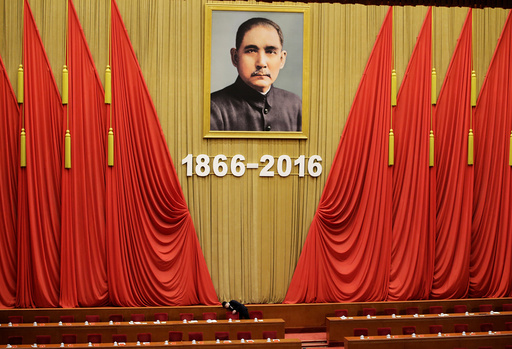 An attendant checks seats after a conference commemorating the 150th birth anniversary of Sun Yat-Sen in Beijing