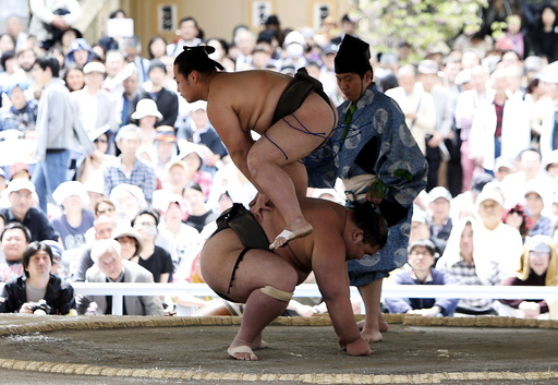 Sumo wrestlers perform a show fight during the annual 'Honozumo' ceremonial sumo tournament dedicated to the Yasukuni Shrine in Tokyo, Japan
