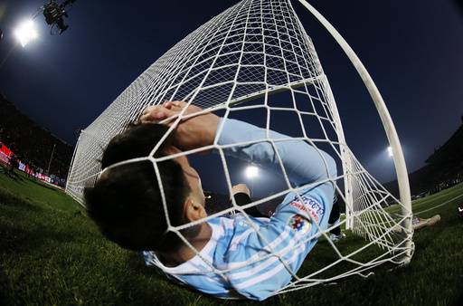 Argentina's Lionel Messi falls in the net during the Copa America 2015 final soccer match against Chile at the National Stadium in Santiago
