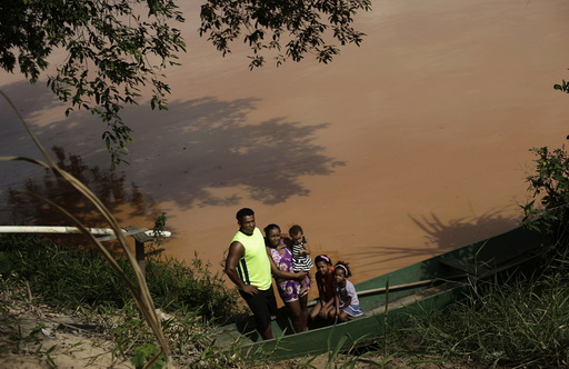 Gilmar, who lives at a farm on the banks of of Rio Doce, which was flooded with mud after a dam, owned by Vale SA and BHP Billiton Ltd burst, poses with his family in Linhares