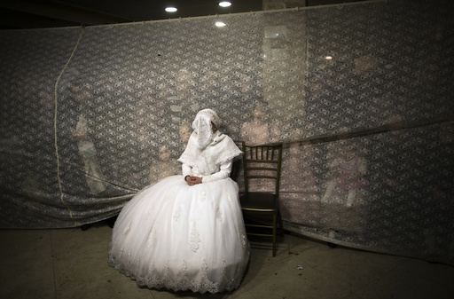 Ultra-orthodox Jewish bride watches her groom dance during their wedding ceremony in Jerusalem