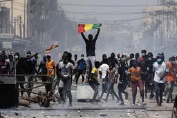 En demonstrant holder opp et senegalesisk flagg under en demonstrasjon fredag. Foto: Leo Correa / AP / NTB
