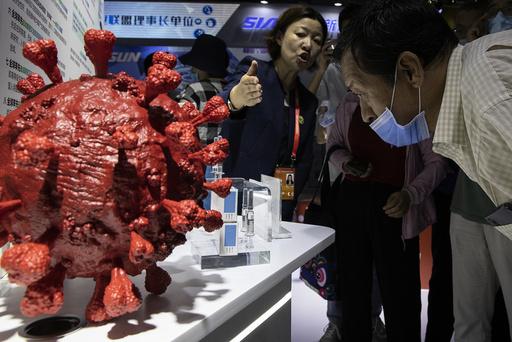 En ansatt svarer på spørsmål om koronavaksinen som er under utvikling av det kinesiske selskapet CNBG, under en messe i Beijing i begynnelsen av september. Foto: Ng Han Guan / AP / NTB