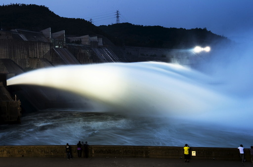 Visitors watch as water gushes from a section of the Xiaolangdi Reservoir on the Yellow River, in Luoyan