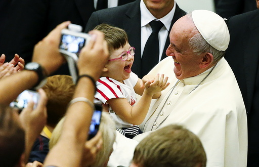 Pope Francis laughs with a baby during a special audience with parish cells for the evangelization in Paul VI hall at the Vatican
