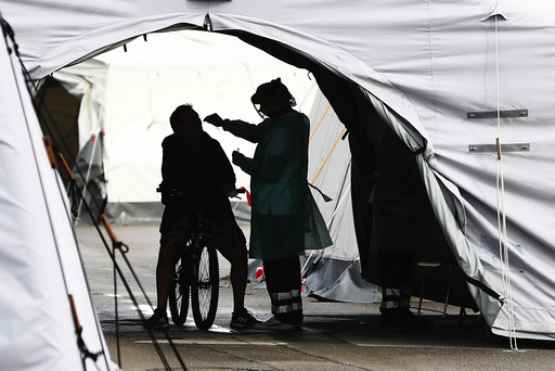 Medical staff member register and take a sample for a voluntary new coronavirus disease test (COVID-19) at a corona test station at the Oktoberfest area 'Theresienwiese in Munich, Germany, Thursday, Sept. 24, 2020. (AP Photo/Matthias Schrader)