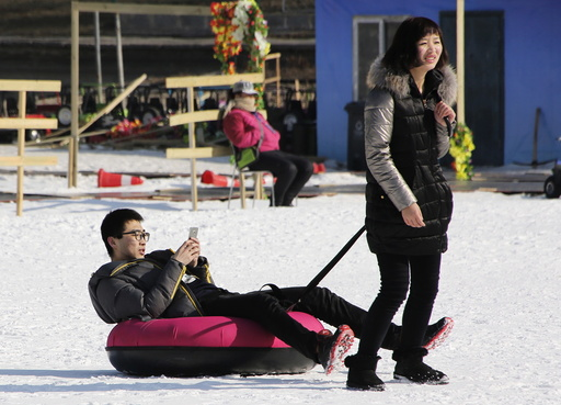A woman toes a tube carrying a man during the Ice and snow carnival at Taoranting park in Beijing