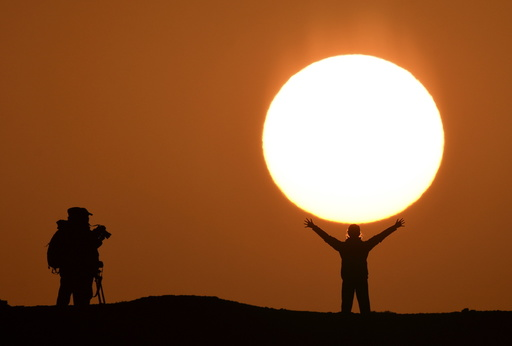 A tourist poses for photographs in front of the rising sun at a tourist resort in Bayingolin Mongol Autonomous Prefecture