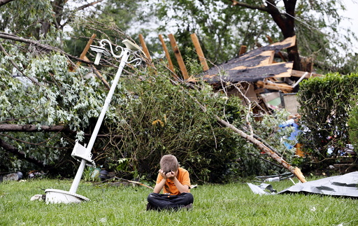 Charles Athrom, 7 sits in front of his destroyed home after a tornado swept through the area in Van, Texas