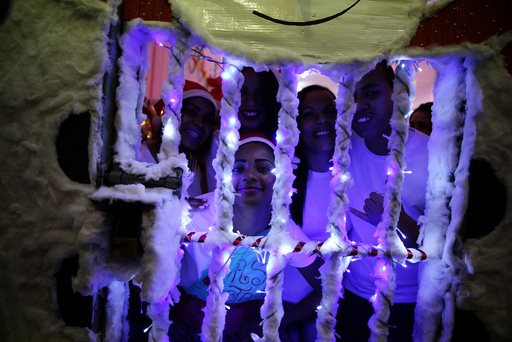 Prisoners look through the bars of their prison cell during a Christmas decorating event