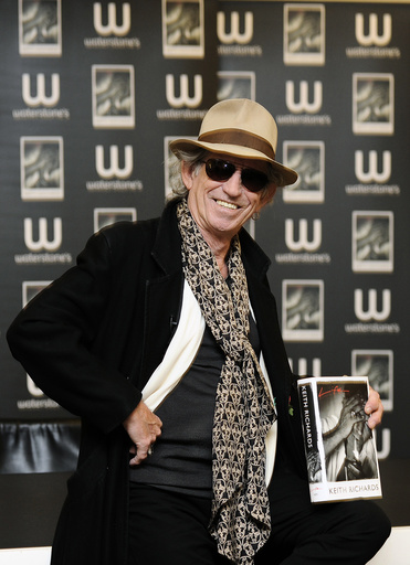 British musician Keith Richards poses for photographers with a copy of his autobiography