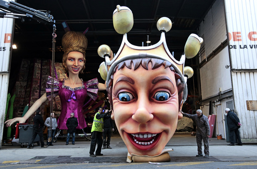 Workers hold a giant figure showing the King of Carnival during preparations for the carnival parade in Nice