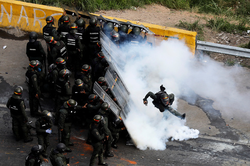 A riot security forces member kicks a tear gas canister during protests at a march to state Ombudsman's office in Caracas