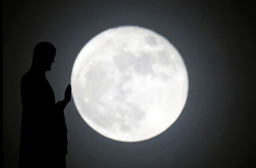 A statue on the roof of Notre-Dame cathedral is silhouetted in front of a supermoon in Paris