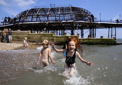 Seven year old Lily Blackburn plays with friends in the sea near the burnt remains of a section of Eastbourne pier, in Eastbourne