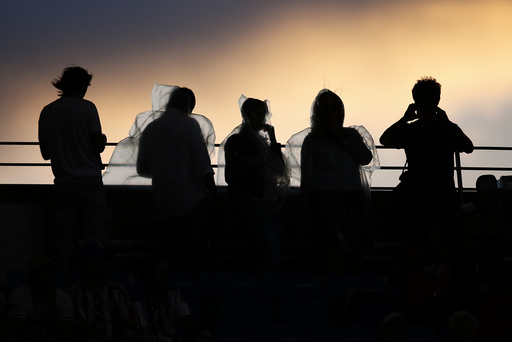 Fans wearing rain ponchos are backlit as they watch the sunset from Arthur Ashe Stadium ahead of the mens final between Federer of Switzerland and Djokovic of Serbia at the U.S. Open Championships tennis tournament in New York