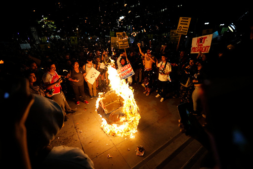 A Donald Trump pinata is burned by people protesting the election of Republican Donald Trump as the president of the United States in downtown Los Angeles