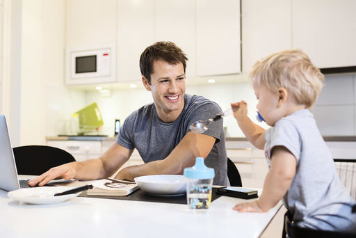Happy father looking at baby boy while using laptop in kitchen