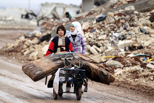 Samah, 11, and her brother, Ibrahim, transport their salvaged belongings from their damaged house in Doudyan village in northern Aleppo Governorate