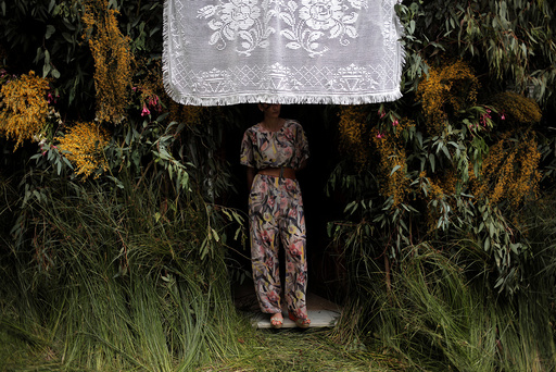 A woman looks out of her house with a decorated doorway during Corpus Christi day in Zahara de la Sierra
