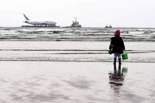 A young girl looks on at a Boeing 767 airplane in the Enniscrone estuary after being tugged from Shannon airport out to sea around the west coast of Ireland