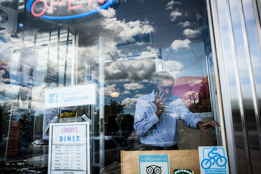 Ohio Gov. John Kasich, a Republican presidential hopeful, takes a call ahead of a walking tour of Main Street during a campaign stop in Keene, N.H.