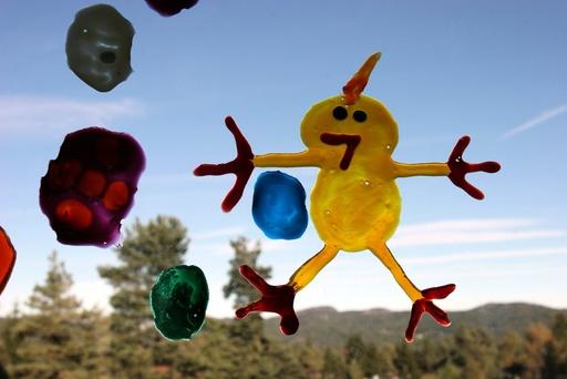 En gul påskekylling er malt på et vindu. Høytid. Påske. Pynt. Kylling. Fjærkre. Utstilling. Barnekunst