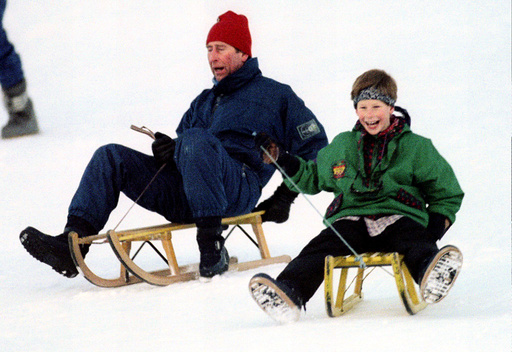 The Prince of Wales (L) and his son Prince Harry share a laugh as they toboggan in Klosters on Janua..