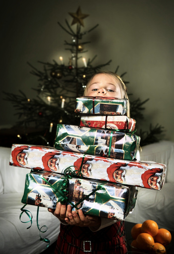 Girl behind pile of Christmas gifts