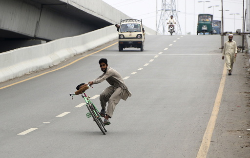 Man does tricks on his bicycle on a highway as the Eid holiday begins in Peshawar