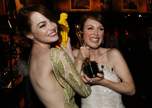 Actress Stone compares her Lego Oscar statuette with actress Moore's genuine Oscar for best leading actress for her role in