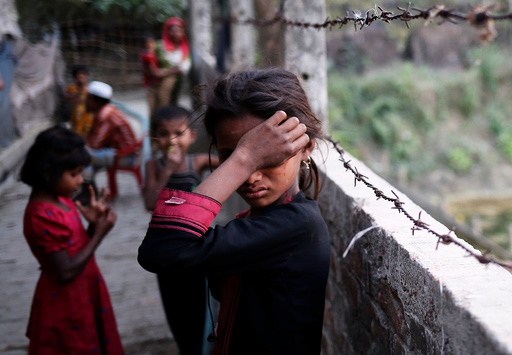A Rohingya refugee girl wipes her eyes as she cries at Leda Unregistered Refugee Camp in Teknaf