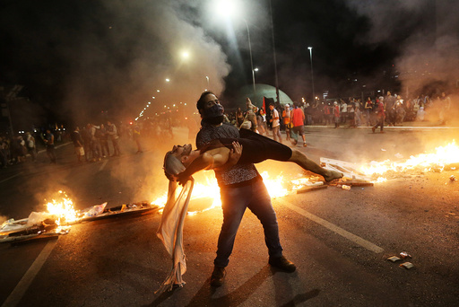 Anti-government demonstrators perform in front of burning barricades as they attend a protest against a constitutional amendment, known as PEC 55, that limit public spending, in front of Brazil's National Congress in Brasilia