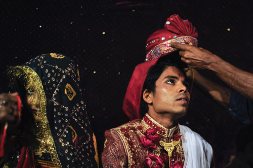 Sanjay wears a turban as he sits beside his wife Jasoda during a mass marriage ceremony in Karachi