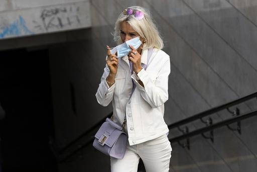 En kvinne tar på seg munnbind idet hun forlater en T-banestasjon i Moskva sentrum. Foto: Aleksander Zemljanitsjenko / AP / NTB