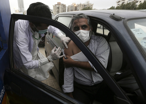 A man receives the Sinovac COVID-19 vaccine from a health worker at a drive-through vaccination center, in Karachi, Pakistan, Saturday, July 31, 2021. (AP Photo/Fareed Khan)