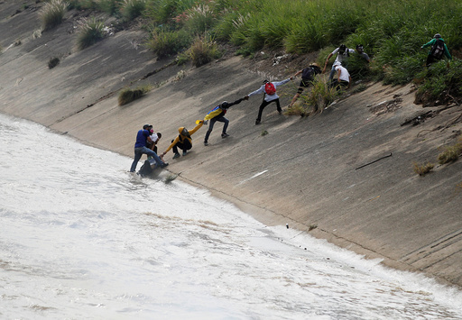 Protesters rescue a fellow protester who fell into the river during a rally in Caracas