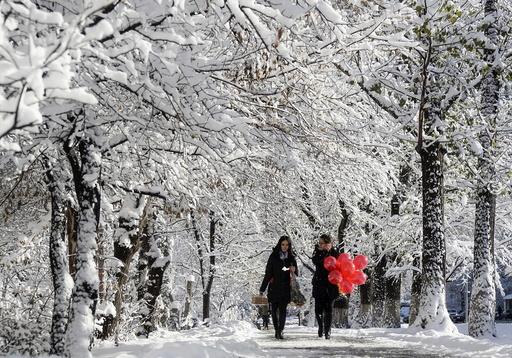 Women walk along snow-covered alley in Almaty, Kazakhstan