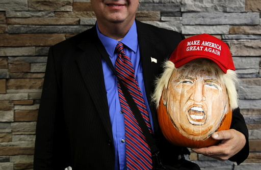 A supporter of U.S. Republican presidential candidate Donald Trump holds a pumpkin painted in the likeness of Trump as he waits to get into a campaign event in Springfield