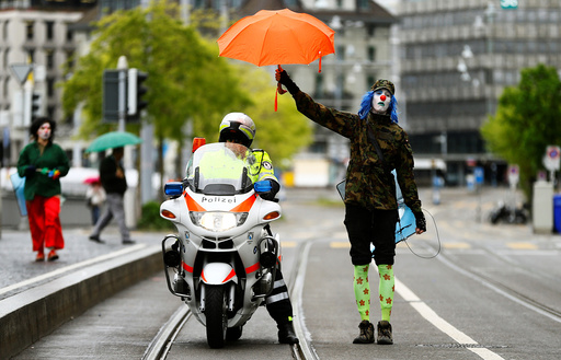A protester dressed as a clown holds an umbrella over a Swiss police officer on a motorbike during a May Day demonstration in Zurich