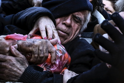 A man grasps a bag of tangerines as people receive free produce, handed out by farmers, during a protest over the government's proposal to overhaul the country's ailing pension system in Athens