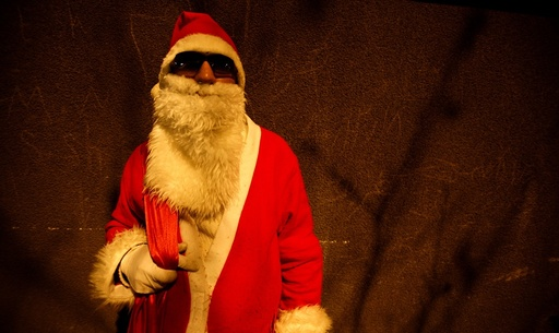 Iranian Christian man dressed as Santa Claus stands outside church during a Christmas Eve mass in Tehran