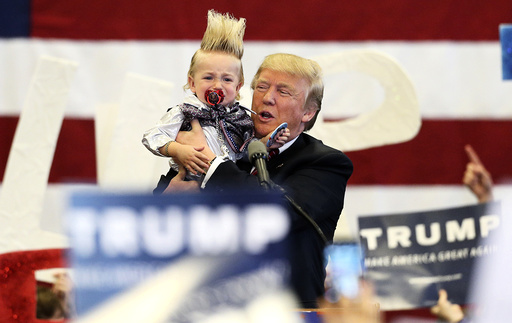 Republican U.S. presidential candidate Donald Trump holds up a crying young child from the crowd as he arrives at a Trump campaign rally in New Orleans, Louisiana